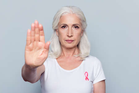 Pretty, attractive, nice woman with Breast Cancer awareness pink ribbon on her white t-shirt, making stop sign with her hand, palm to the camera over grey background