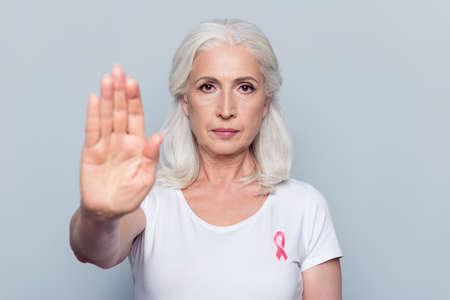 Mooie, aantrekkelijke, mooie vrouw met borstkanker bewustzijn roze lint op haar witte t-shirt, stopbord maken met haar hand, palm naar de camera over grijze achtergrond