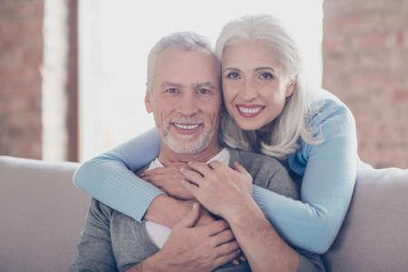 2人の幸せな古い既婚者の肖像画をクローズアップ、彼らは抱きしめ、完璧な光沢のある白い笑顔を持っています