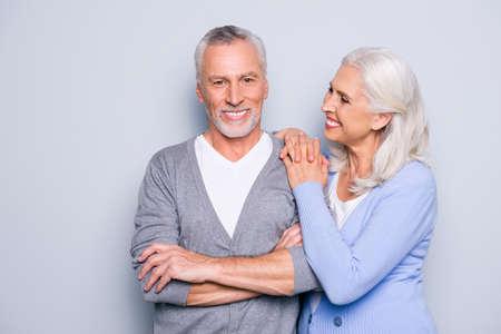 De gelukkige opgewekte mooie tedere zachte leuke bejaarde mensen glimlachen en omhelzen, geïsoleerd op grijze achtergrond