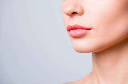 Cropped close up photo of beautiful woman's lips with shape correction, isolated on grey background, copyspace 스톡 콘텐츠
