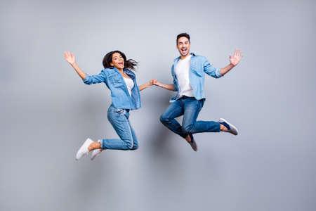 Er gegen Sie Ganzaufnahme von attraktivem, spielerischem, nett, hispanisches Paar in der zufälligen Ausstattung, die mit geöffneten Mündern über grauem Hintergrund springt