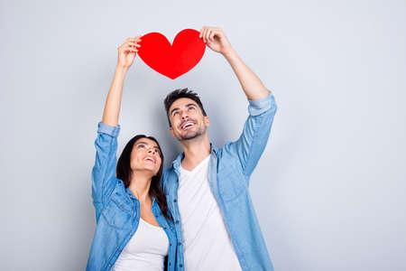 Liefdesverhaal van caucasion mooi mooi paar in casual outfit, jeans shirt bedrijf, opstaan, kijkend naar rood hart samen, staande over grijze achtergrond Stockfoto
