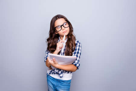 Education, study, intelligence, health care, lifestyle pre teens concept. Charming cute attractive adorable lovely school girl in fashionable outfit with books and in specs analyzing something