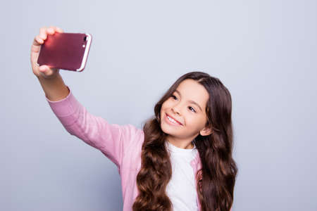 Childhood, addiction to self shots, telephone, technology, internet, social nets, pre teens concept. Charming hispanic ethnicity school girl in fashionable outfit makes takes photo on her pda
