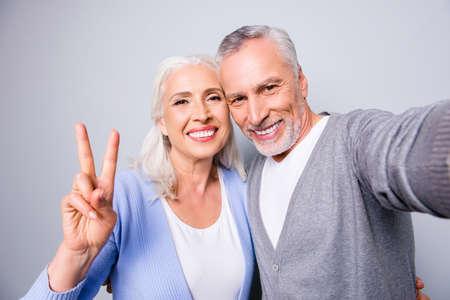 ¡Felices recuerdos dulces! Close up foto de pareja senior mostrando dos dedos y tomando un selfie, aislado sobre fondo gris