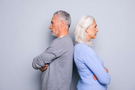Concept of misunderstanding and  communicative problem between two senior people, they are standing back to back, isolated on grey background Stock Photo