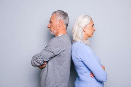 Konzept des Missverständnisses und des Kommunikationsproblems zwischen zwei älteren Leuten, stehen sie zurück zu der Rückseite, lokalisiert auf grauem Hintergrund