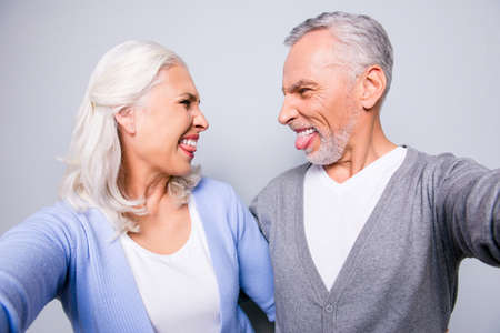 Close up photo of crazy happy mad old people, they are taking a selfie on a tablet, isolated on grey background