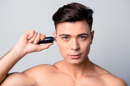 Close up portrait of handsome young confident guy with perfect skin, he is using electric machine to get rid of unwanted hair in airs, isolated on grey background