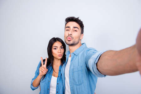 Sweet, attractive, hispanic, caucasian couple - man making self portrait, woman showing peace symbol, they sending kiss to the camera, standing over grey background
