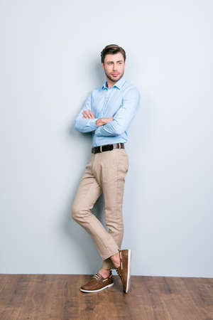 Vertical full length portrait of half turned, confident, handsome, stunning man with crossed hands standing near grey wall on wooden floor looking to the side Stock Photo