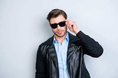 Portrait of cool, stylish macho with stubble  holding hand on eyelet of black glasses, looking at camera over grey background