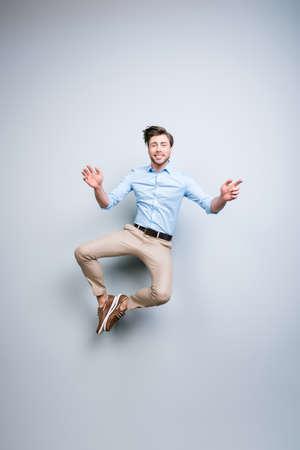 Felice, giovane, barbuto, attraente uomo bello e sorridente in abito classico che salta in aria mettendo insieme i suoi piedi su sfondo grigio