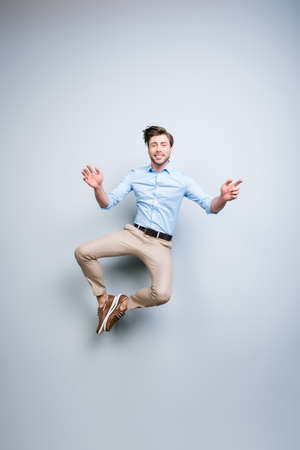 Glücklicher, junger, bärtiger, attraktiver hübscher, lächelnder Mann in der klassischen Ausstattung, die in einer Luft zusammensetzt seine Füße über grauem Hintergrund springt