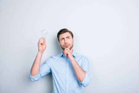Close up portrait of thinking student with bristle looking up with idea, touching his chin and holding a light bulb in his hand while standing over grey background