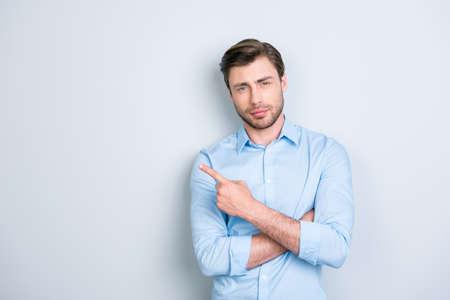 Advertentie concept. Portret van schattige, ideale, blanke man in shirt, wijzen en kopieer ruimte met gekruiste armen, kijkend naar de camera, permanent over grijze achtergrond Stockfoto