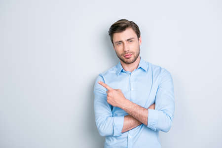 Advertisement concept. Portrait of cute, ideal, caucasian man in shirt, pointing and  to copy space with crossed arms, looking at camera, standing over grey background