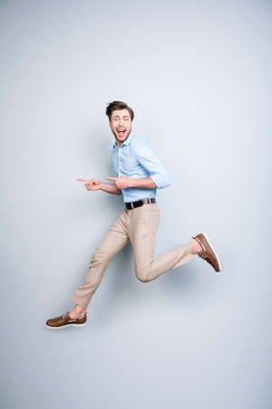 Happy, young, bearded, funny, attractive handsome man in shirt, pants  jumping in air and pointing index fingers to the side over grey background