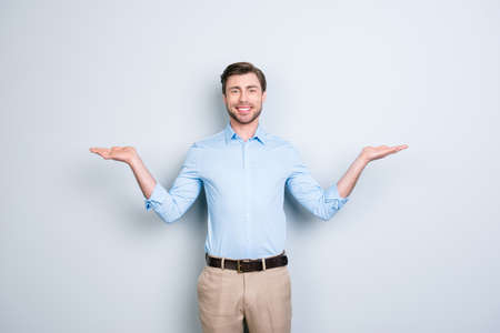 Portrait of successful, cheerful, cute, young man presenting start up, new product showing copy space on his palms in two sides, looking at camera, standing over grey background