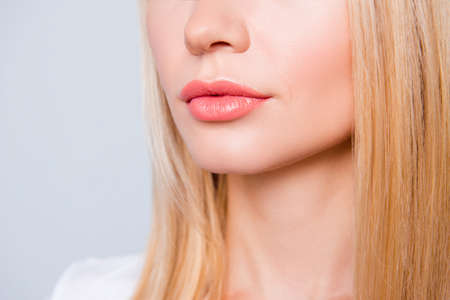 Close up photo of woman's skin with expression wrinkles, blonde hair and lips with moisturizing balm on them. She is isolated on grey background Zdjęcie Seryjne - 91688046