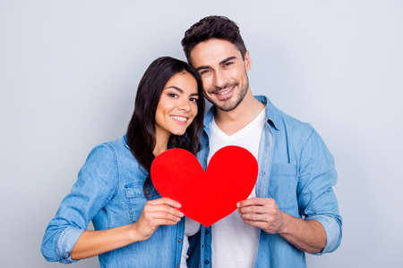 He vs she together forever. Love story of caucasion beautiful lovely hispanic cute couple holding red heart together standing over grey background Stockfoto