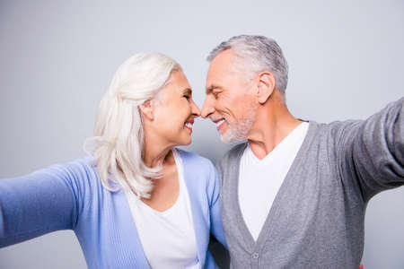 Close up photo of two happy cheerful lovely tender gentle sweet senior couple, they are taking a self portrait, hugging each other and touching noses, isolated on grey background