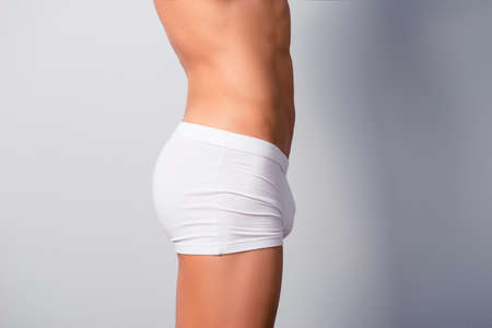 Concept of intimate man's health. Size profile photo of sportive athletic man's body, he is wearing white boxers, isolated on grey background, copy space