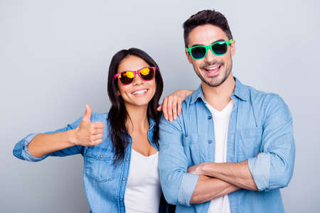 Attractive cool beautiful partners in summer glasses smiling to the camera, girl making thumb up sign, man with crossed hands over grey background Stock Photo
