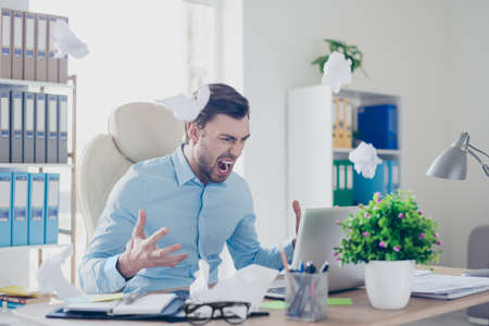 Frustrated angry annoyed disappointed head of a company is not satisfied with work of his employees, he is screaming and throwing scraps of paper, sitting in front on his netbook Stock Photo - 91652354