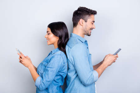 Beautiful, pretty, cute woman and handsome man in jeans shirts standing back to back and writing sms through 3g internet on smart phones over grey background Фото со стока