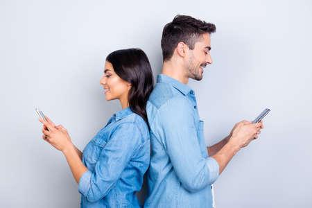 Piękna, ładna, urocza kobieta i przystojny mężczyzna w dżinsowych koszulach stojących plecami do siebie i piszących sms przez internet 3g na smartfonach na szarym tle