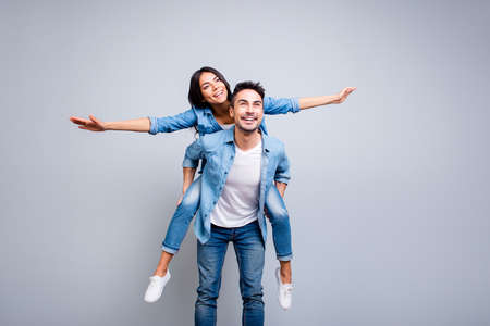 I believe I can fly. Love story of attractive, funny, cheerful couple - handsome man carrying his lover on back like plane, woman opens her hands to the side over grey background