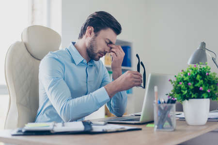 I'm exhausted, I can't continue working! Tired sad depressed office worker clothed in stylish blue shirt, holding his black rimglasses and touching nose-bridge with closed eyes
