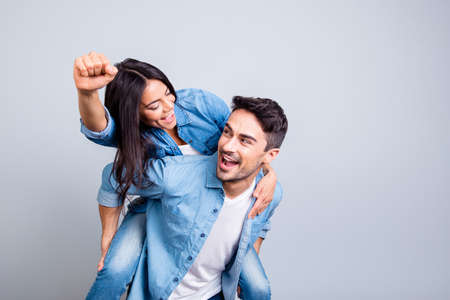 Crazy lovely lovers celebrating a victory, looking to each other, woman raised her hand with fist up in piggy back style over grey background Standard-Bild