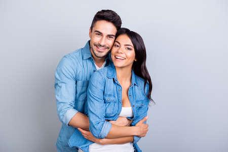 Retrato de alegre linda pareja linda con radiantes sonrisas abrazando y mirando a la cámara sobre fondo gris