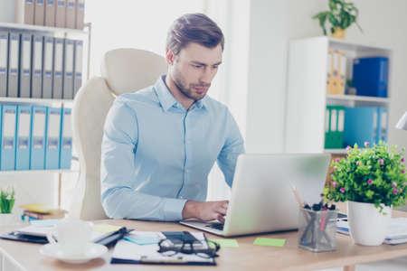 Portret van zelfverzekerd ernstig geconcentreerd hardwerkend bezig met het dragen van formele kleding systeembeheerder, werkt hij software op moderne laptop in kantoor bij