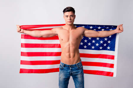 Portrait of confident handsome shirtless guy wearing jeans, he is holding flag of the USA on his back, isolated on grey background Stock Photo