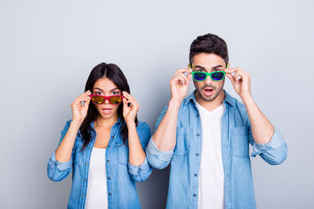 おやまあ!広い口と目を持つショックを受けたパートナーは、灰色の背景の上に夏の眼鏡を覗き見