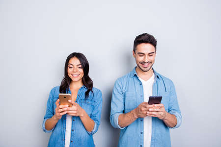 attractive, cheerful, smiling lovers in casual outfit, jeans shirts  having smart phones in hands, looking at screen, texting with each other, using 5g internet, standing over grey background Stockfoto