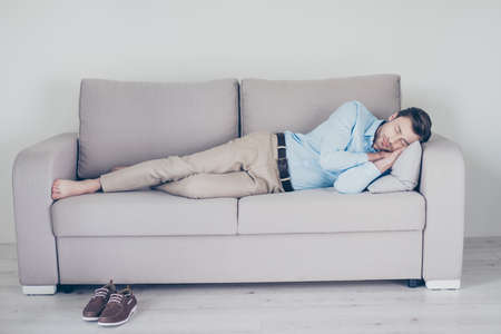 Tired overworked sleepy wearing blue shirt and beige trouser employee is having a daydream on a sofa on cushion Stock Photo