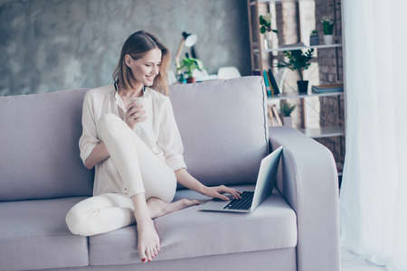 Beautiful smiling blonde woman sitting on couch using wi fi internet on her laptop for  online shopping  holding cup of tea 스톡 콘텐츠