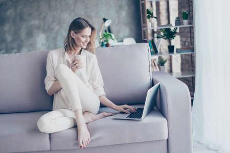 Schöne lächelnde Blondine, die auf Couch unter Verwendung des Wi-Fi-Internets auf ihrem Laptop für das on-line-Einkaufen hält Tasse Tee sitzen