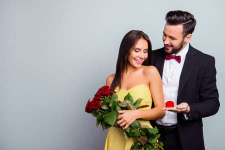 Portrait with copy space of attractive family, couple in formal wear, sexy wife in dress holding bouquet of red roses, husband in tuxedo embracing her from back side and presenting a case with ring