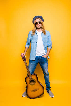 Vertical full length portrait of professional, successful musician in hat and glasses holding hand in pocket, stand guitar on the floor over yellow background