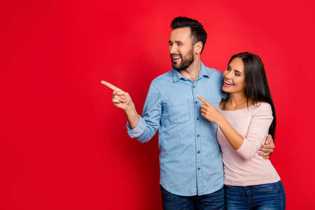 Portrait of smiling, embracing, excited, attractive couple pointing to copy space with forefinger over red background, having date Foto de archivo