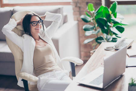 Nice, independent, cute woman in white suit, formal wear, glasses sitting on chair at her desk in office, holding arms behind the head with close eyes, thinking about holidays, vacation Foto de archivo