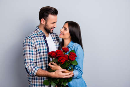 Beautiful, happy, positive couple embracing, looking to each other, holding bouquet of red roses over grey background, 14 february, young, cute family going to be parents 免版税图像 - 92490819