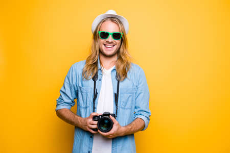 Give me  smile. Cheerful attractive young journalist in glasses, hat, casual outfit using photo camera over yellow background Stok Fotoğraf