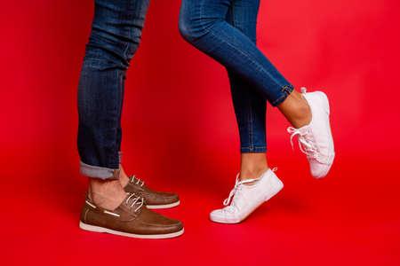 Close-up foto van vrouw en man benen in jeans, broek en schoenen, meisje met opgeheven been, stijlvolle paar kussen tijdens datum, geïsoleerd op rode achtergrond, hij vs zij